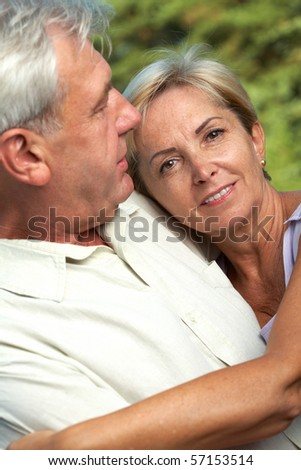 Mature woman embracing her husband. Focus on the woman. - stock photo