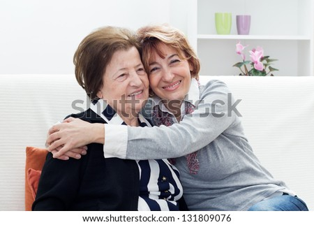 Mature woman embracing her mother and sitting on the couch in the living room. - stock photo