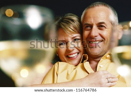 Mature woman embracing his husband between two glasses of white wine - selective focus