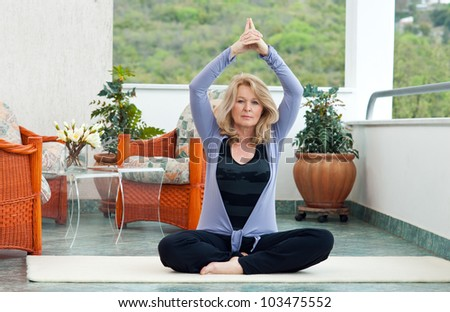 mature woman exercise on her balcony - stock photo