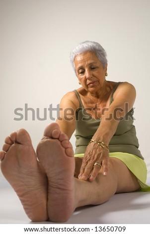 Mature woman exercising at home - stock photo