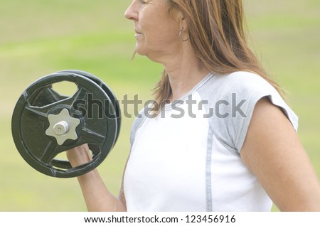 Mature woman exercising outdoors, lifting weight to strengthen bicep muscle, isolated with green blurred background and copy space. - stock photo