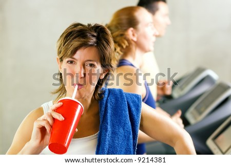 Mature woman has a refreshing softdrink after a workout on the treadmill