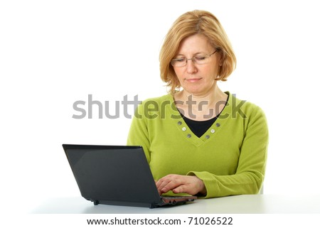 mature woman in green top and glasses works on her netbook, isolated on white - stock photo