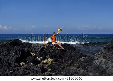 """Mature woman in her mid 50's is retiring early and celebrating the occasion.  She is ready to throw her straw hat in the air and wave her scarf """"hello"""" to the Big Island of Hawaii and a new life. - stock photo"""