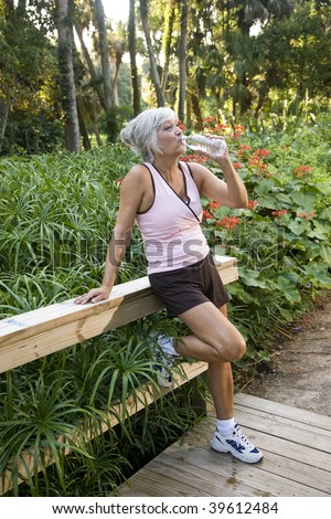 Mature woman in her 50s in workout clothes drinking a bottle of water, standing on wooden bridge in park - stock photo