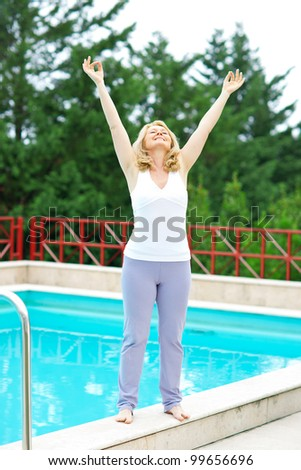 mature woman in relaxation happy pose in front of the pool