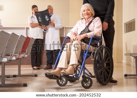 Mature woman in wheelchair in the hospital with her husband. Doctors analyzing scan in background. - stock photo