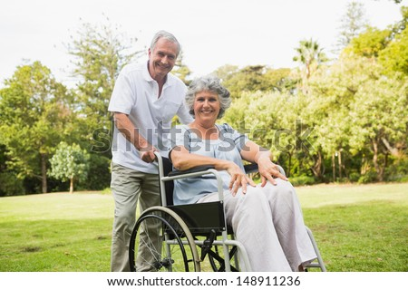Mature woman in wheelchair with partner smiling at camera at the park - stock photo