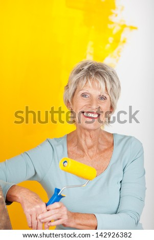 Mature woman is painting a wall in yellow - stock photo