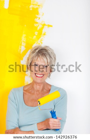 Mature woman keeping busy, while painting her walls - stock photo