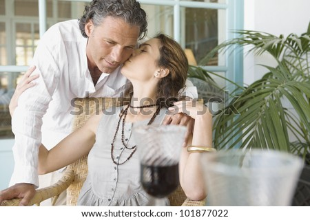 Mature woman kissing man while having a red wine drink at home. - stock photo