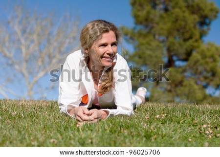 mature woman laying in grass in a park smiling - stock photo