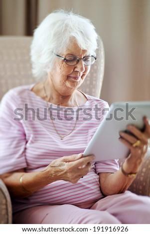 Mature woman looking at her digital tablet, tilt shift, selective focus - stock photo