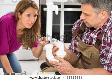 Mature Woman Looking At Male Plumber Repairing Pipe Of Sink - stock photo