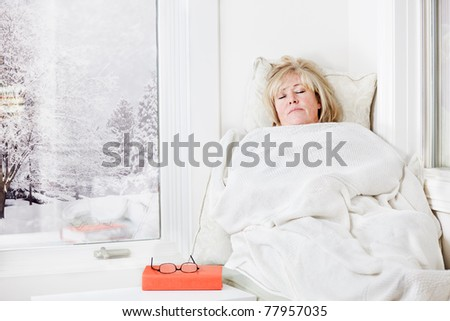 Mature woman lying down taking a nap under a warm blanket - stock photo