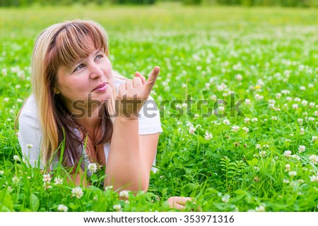mature woman on a green meadow showing a finger in the direction - stock photo