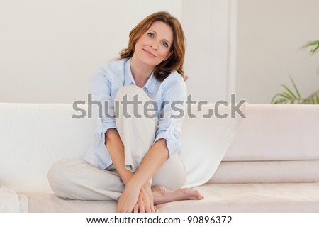 Mature woman on the couch - stock photo