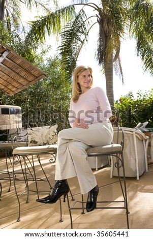 Mature woman on tropical vacation at a resort sitting outdoors - stock photo