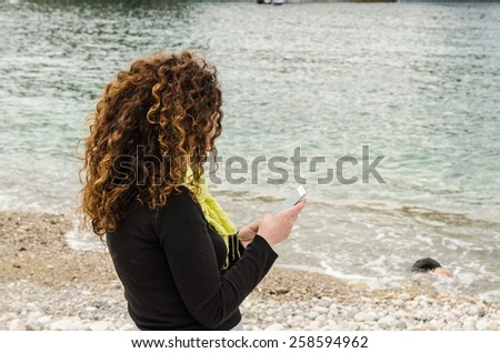 Mature Woman on vacation, go to the beach to find herself, and use smartphone, solitude. - stock photo