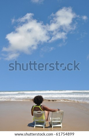 Mature Woman on Vacation sitting alone on Beach