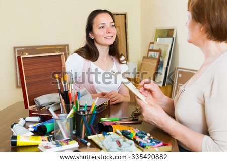 Mature woman painting portrait of girl at workshop - stock photo
