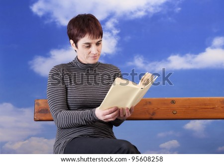 mature woman reading a book, sitting on a bench