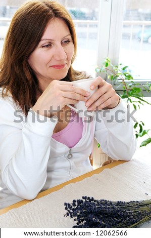 Mature woman relaxing at home holding a cup - stock photo