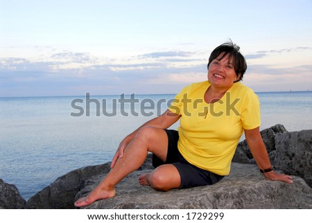 Mature woman relaxing on a shore - stock photo