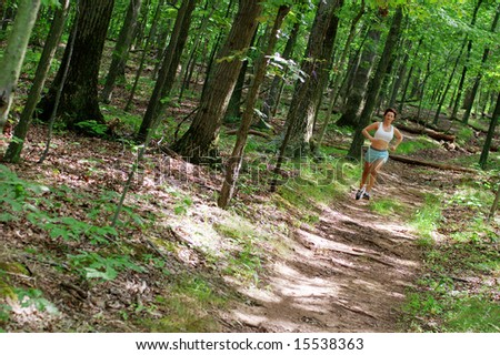 Mature woman running in forest.