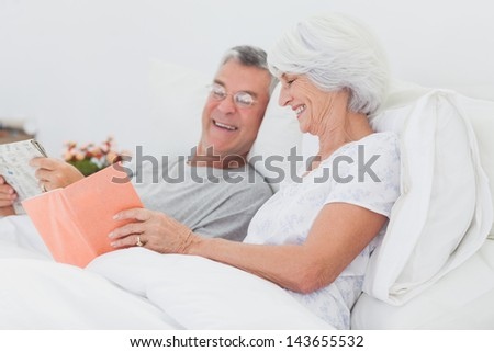 Mature woman showing her book to her husband - stock photo