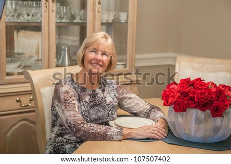 Mature woman sitting at dining table with red roses.