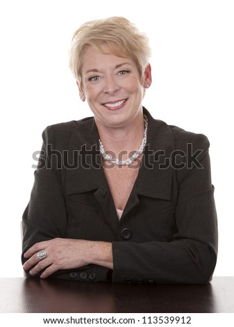 mature woman sitting behind desk on white background - stock photo