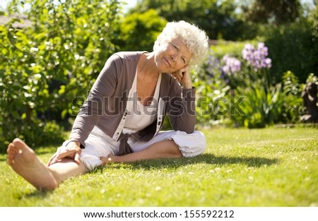 Mature woman sitting down on grass comfortably in garden looking at you - Outdoors - stock photo