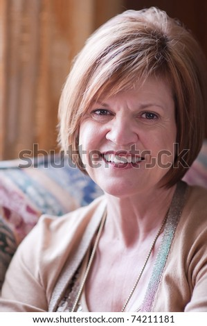 Mature 50+ woman sitting in light by window displaying positive and confident smile in portrait orientation - stock photo