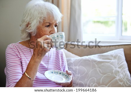 Mature woman sitting inside sipping her tea - stock photo