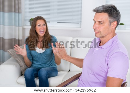 Mature Woman Sitting On Sofa Arguing With Man At Home - stock photo