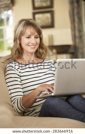 Mature Woman Sitting On Sofa At Home Using Laptop