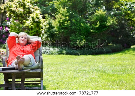 Mature woman sitting & thinking outside - stock photo