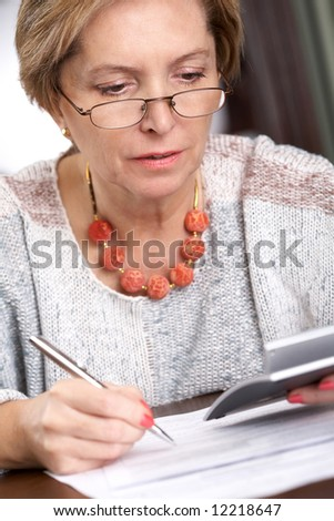 Mature woman sitting with calculator over documents - stock photo