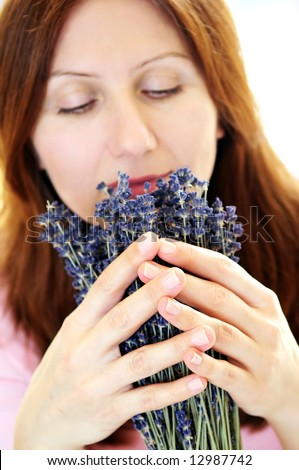 Mature woman smelling lavender flowers focus on hands - stock photo