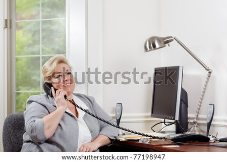 Mature woman smiles as she talks on the phone - stock photo