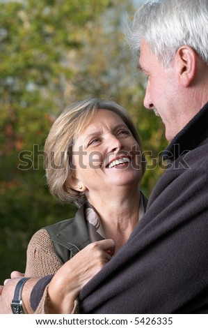 Mature woman smiles to her man, focus on woman. - stock photo