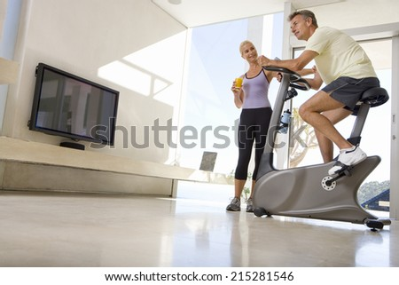 Mature woman smiling at mature man riding stationary bicycle in living room, low angle view - stock photo
