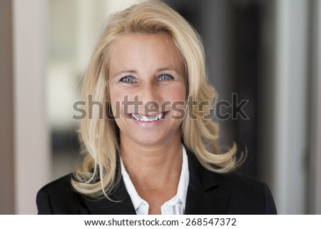 Mature woman smiling at the camera. She is successful and got a lot of leadership. - stock photo