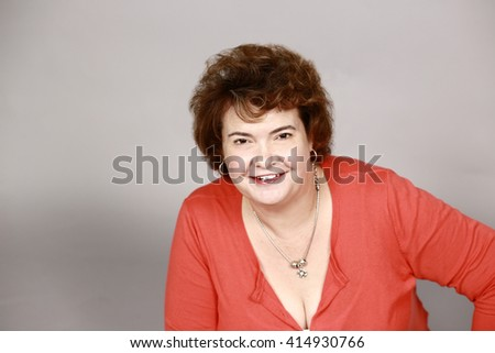 mature woman smiling on gray background