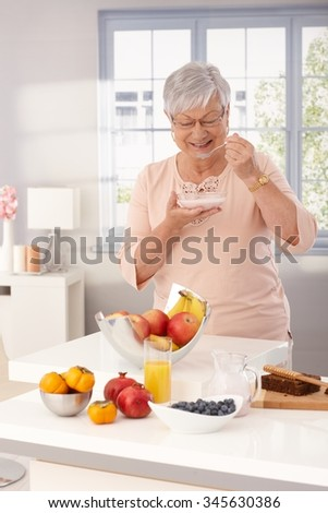 Mature woman standing by kitchen counter, eating breakfast cereal. - stock photo