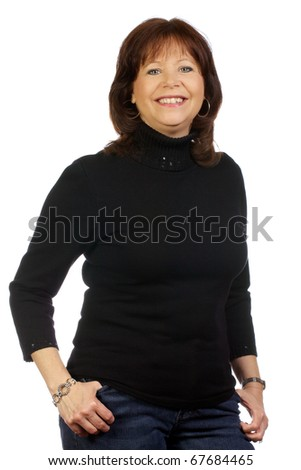 Mature woman standing with her thumbs in her pockets looking happily at the camera. - stock photo