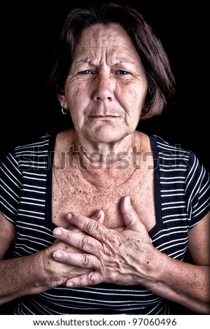 Mature woman suffering from chest pain or depression on a black background - stock photo