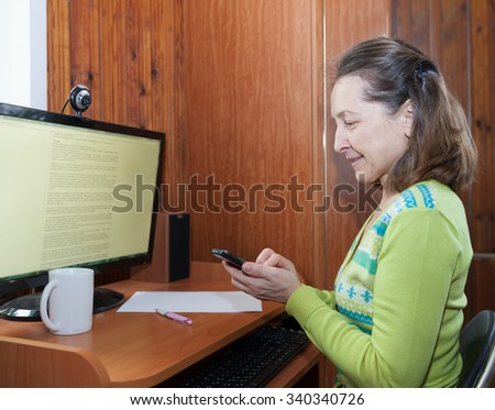 Mature woman talking on   mobile phone near   computer